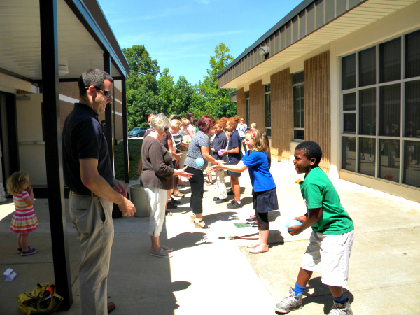 Mentor Matt Swift joins his lunch buddy, Cory in a water balloon toss at Southwest Elementary School.